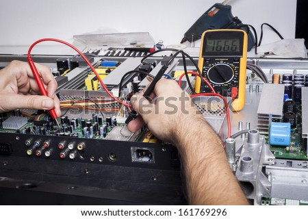 Electronics Repair service with red probe and capacitors on electronic board