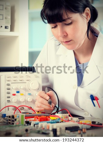 Electronics tech tests a surcuit board, tinted image - stock photo
