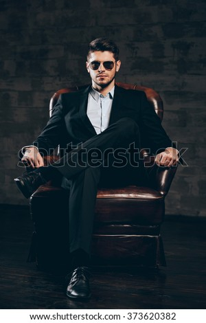 Elegance and masculinity.Young handsome man in suit and sunglasses holding hand on chin and looking at camera while sitting in leather chair against dark grey background - stock photo