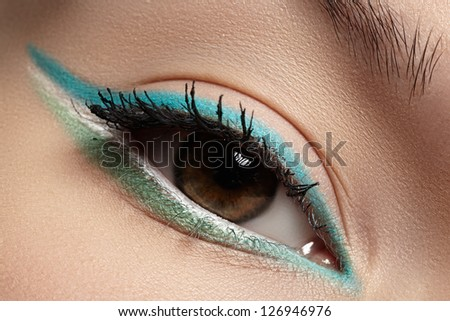 Elegance close-up of beautiful female eye with fashion trend mint colors eyeshadow and eyeliner. Macro shot of beautiful woman's face part with makeup. Cosmetics, beauty and make-up - stock photo