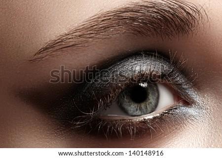 Elegance close-up of female eye with dark gray eyeshadow. Macro shot of beautiful woman's face part. Wellness, cosmetics and make-up. - stock photo