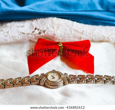 Elegance - red ribbon, hand watch on white lace and royal blue satin. - stock photo