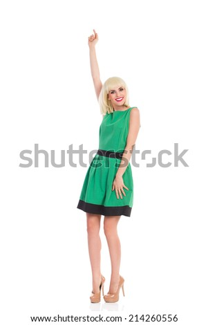 Elegance smiling blonde woman posing in green dress, raising arm and pointing up.  - stock photo