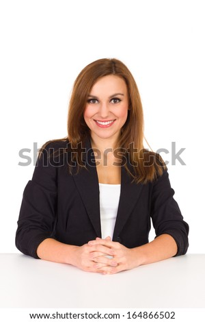 Elegance young beautiful woman sitting at the desk and smiling at camera. Head and shoulders shot isolated on white. - stock photo