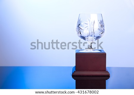Elegant and classy crystal cup trophy on blue hue ambient - stock photo