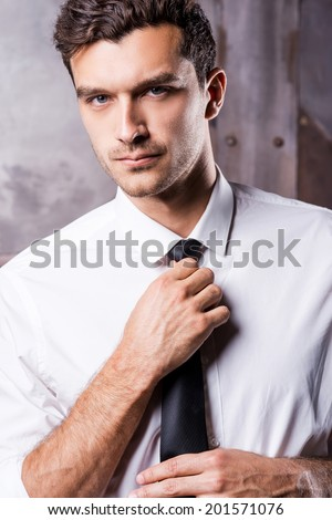 Elegant and handsome. Handsome young man in formalwear adjusting his necktie and looking at camera  - stock photo