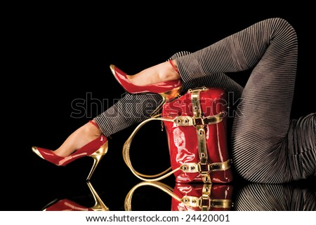 Elegant and relaxed. A close-up of lady's pretty legs in red shoes posing with a leather red bag on a mirror surface. - stock photo