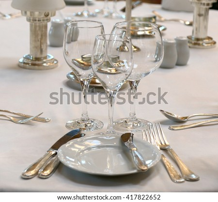 Elegant and simple fine dining table setting with cutlery and crockery on white table linen - stock photo