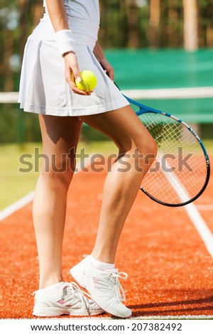 Elegant and sporty. Close-up of beautiful woman in sports clothing holding tennis racket and ball while standing on court