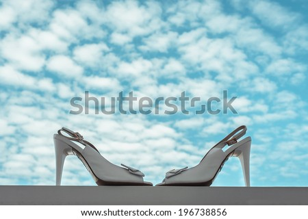 Elegant and stylish bridal shoes against a cloudy sky