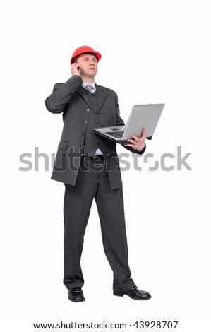 Elegant architect in red helmet standing with open laptop and talking by mobile phone. Isolated on a white background. - stock photo