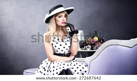 Elegant attractive blonde woman posing in hat and fashionable pinup dress. - stock photo