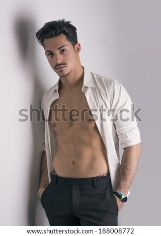 Elegant attractive young man with white shirt open on naked torso, leaning against wall
