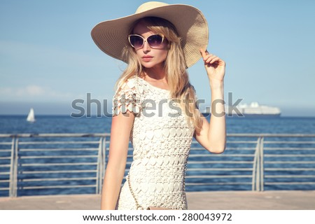 Elegant attractive young woman posing in sunglasses and hat on vacation day. Sea on background. Blue sky.