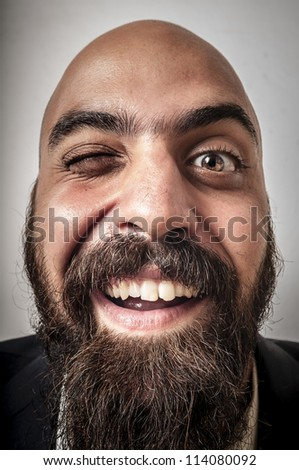 elegant bearded man with jacket who winks on white background - stock photo