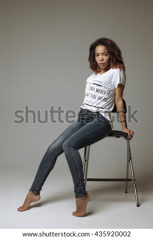 Elegant beautiful African American woman sitting in a contemporary chair