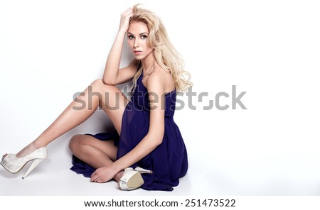 Elegant beautiful blonde woman posing in studio, looking at camera. - stock photo