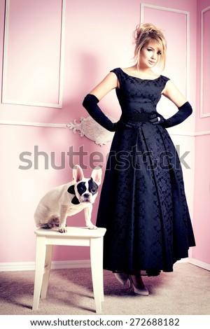 Elegant beautiful blonde woman posing with pug dog over pink background. - stock photo