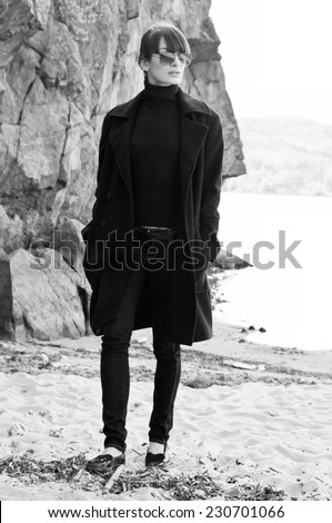 Elegant beautiful brunette woman model wearing tutpleneck sweater, coat, jeans, sunglasses, walking along the beach near rocks on a bright sunny day. Autumn fashion. High key portrait - stock photo