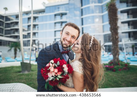 Elegant beautiful couple posing near modern glass building