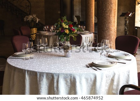 Elegant beautiful decorated table with utensils, vases of flowers and tableware. Close up. Wedding concept