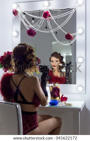 elegant beautiful sexy girl in lace lingerie in a retro style with beautiful hair and makeup in the style of 20-ies sitting in the dressing room near the mirror - stock photo