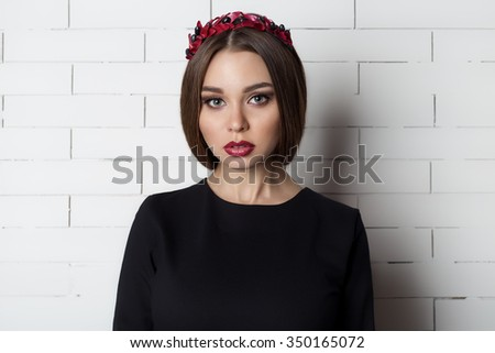 elegant beautiful sexy woman in evening dress with a bright evening make-up with full lips with red lipstick on her lips , and with a wreath of olive branches on her head - stock photo