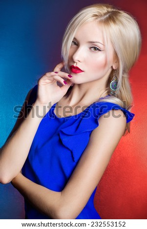 elegant beautiful women blonde with red lips in a blue dress in the Studio - stock photo