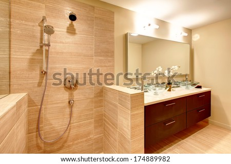 Elegant beige bathroom with shower. Glass vessel sinks  perfectly match with white flowers, brown wood cabinets and mirror - stock photo