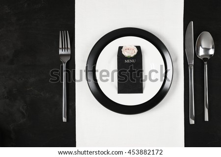 Elegant black and white table setting: plates on linen, blank label with rose and silverware. Top view point.