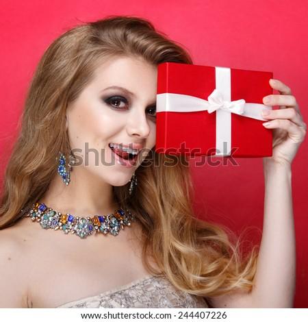 Elegant blonde woman holding small gift box with ribbon. Studio portrait over red background. Happy birthday. Valentines Day. Joyful - stock photo