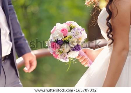 elegant bridal bouquet in bride's hand - stock photo