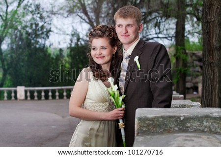 Elegant bride and groom posing outdoors in the park