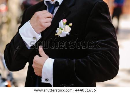 Elegant bride in a black jacket, straightens his tie, close-up - stock photo