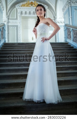 Elegant bride in a white dress standing on the stairs