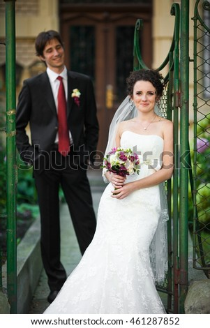 Elegant bride leans to the green fence while groom stands on the background