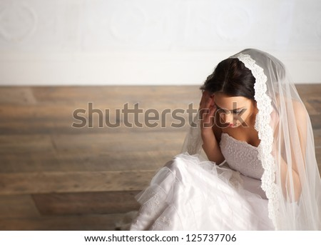 Elegant bride sitting on the floor with veil over her head - stock photo