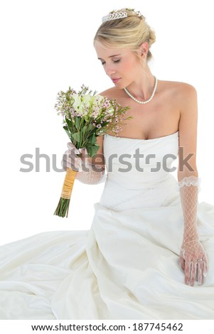 Elegant bride with eyes closed smelling flower bouquet over white background