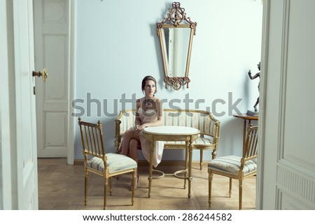 elegant brunette girl in luxury room sitting on vintage sofa with classic hair-style, precious necklace and pink dress. Aristocratic style and antiques furnitures - stock photo