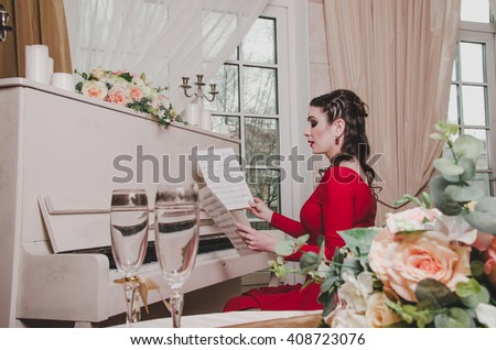 Elegant brunette woman pianist in evening red dress sits at the retro piano, looking on musical notes in classic style interior. Music concept. Vintage objects flowers, candles, glasses. - stock photo