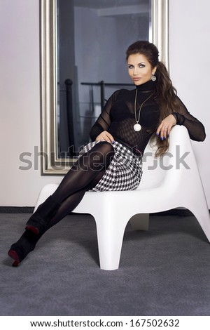 Elegant brunette woman sitting, looking at camera. - stock photo