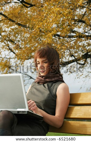 Elegant brunette woman sitting with laptop on the bench in the autumn park