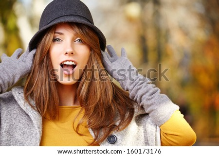 Elegant brunette  woman standing in a park in autumn  - stock photo