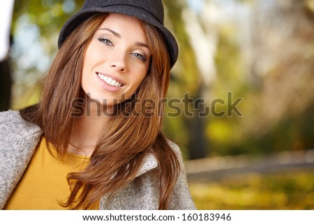 Elegant brunette  woman standing in a park in autumn