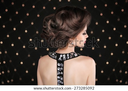 Elegant Brunette woman with hairstyle. Fashion glamour lady with gemstone on back posing against the bokeh lights background.