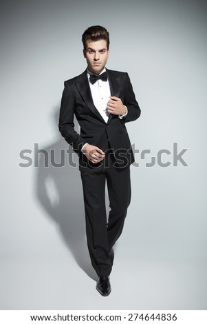 Elegant business man fixing his collar while walking on studio background. - stock photo