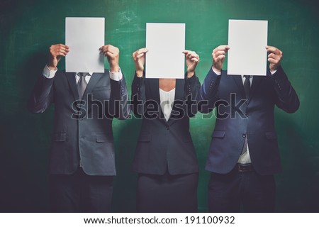 Elegant business partners holding blank papers on green background - stock photo