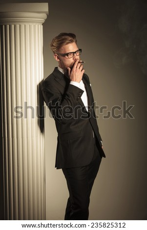Elegant business smoking a cigarette near a white column while looking away, holding one hand in his pocket. Side view picture. - stock photo