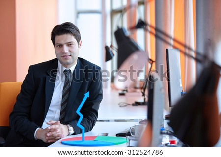 Elegant businessman analyzing data in office - stock photo