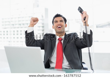 Elegant businessman cheering with telephone receiver in front of laptop at office desk - stock photo